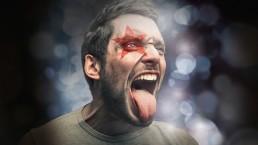 Mann mit gemaltem Starmix-Stern am Auge streckt Zunge raus